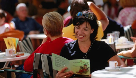 Happy woman in a cafe reading a brochure