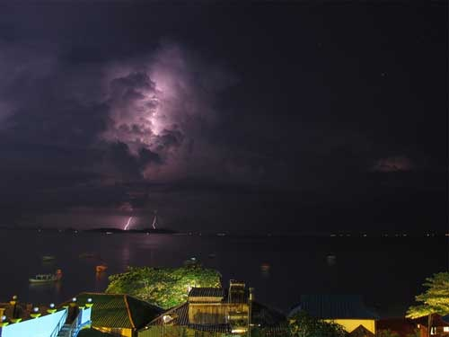 Lighting striking over beach