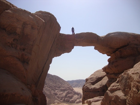 Man standing on top of rock arch