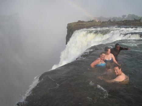 Group swimming near waterfall