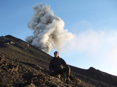 Man standing next to volcano