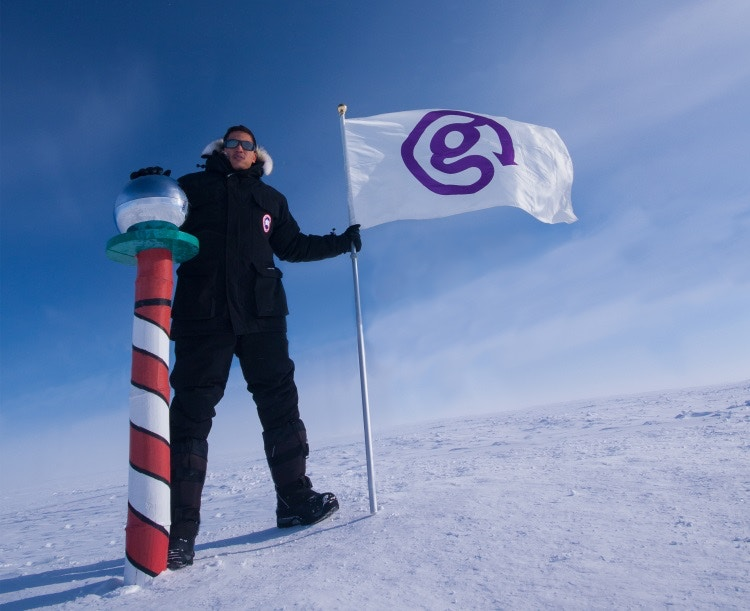Bruce planting the G flag at the South Pole. Image courtesy of G Adventures.