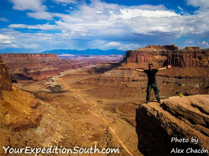 Alex stands with both arms extended on a rocky rim overlooking the enormous rust-coloured valleys of the Grand Canyon