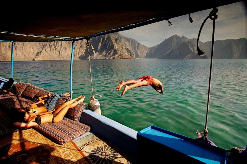 Man diving off tour boat cruising Musandam Coast.