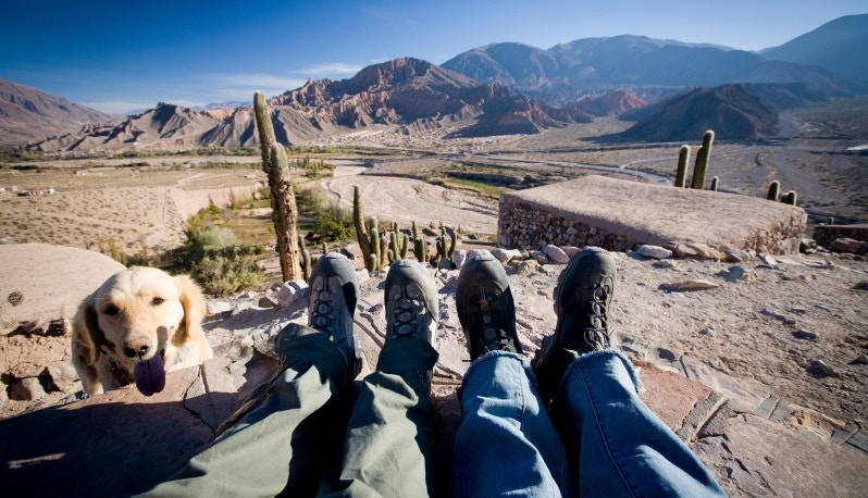 View of couple's feet and local dog with Andes in distance.