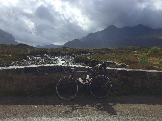 Cycling over a stone bridge overlooking the Cuillin Hills