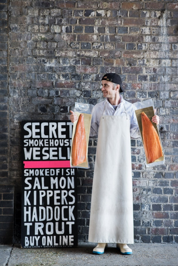 Max Bergius of Secret Smokehouse in London Fields holds up some salmon in East London © Issy Croker / Lonely Planet