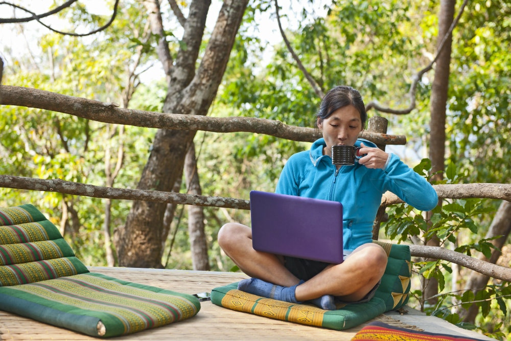 A woman in a treehouse drinks tea while on her laptop