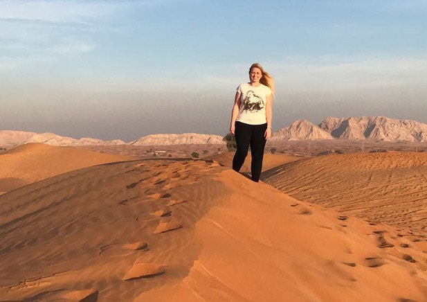 Kat stood on a sand dune with an impressive desert view stretching into the distance