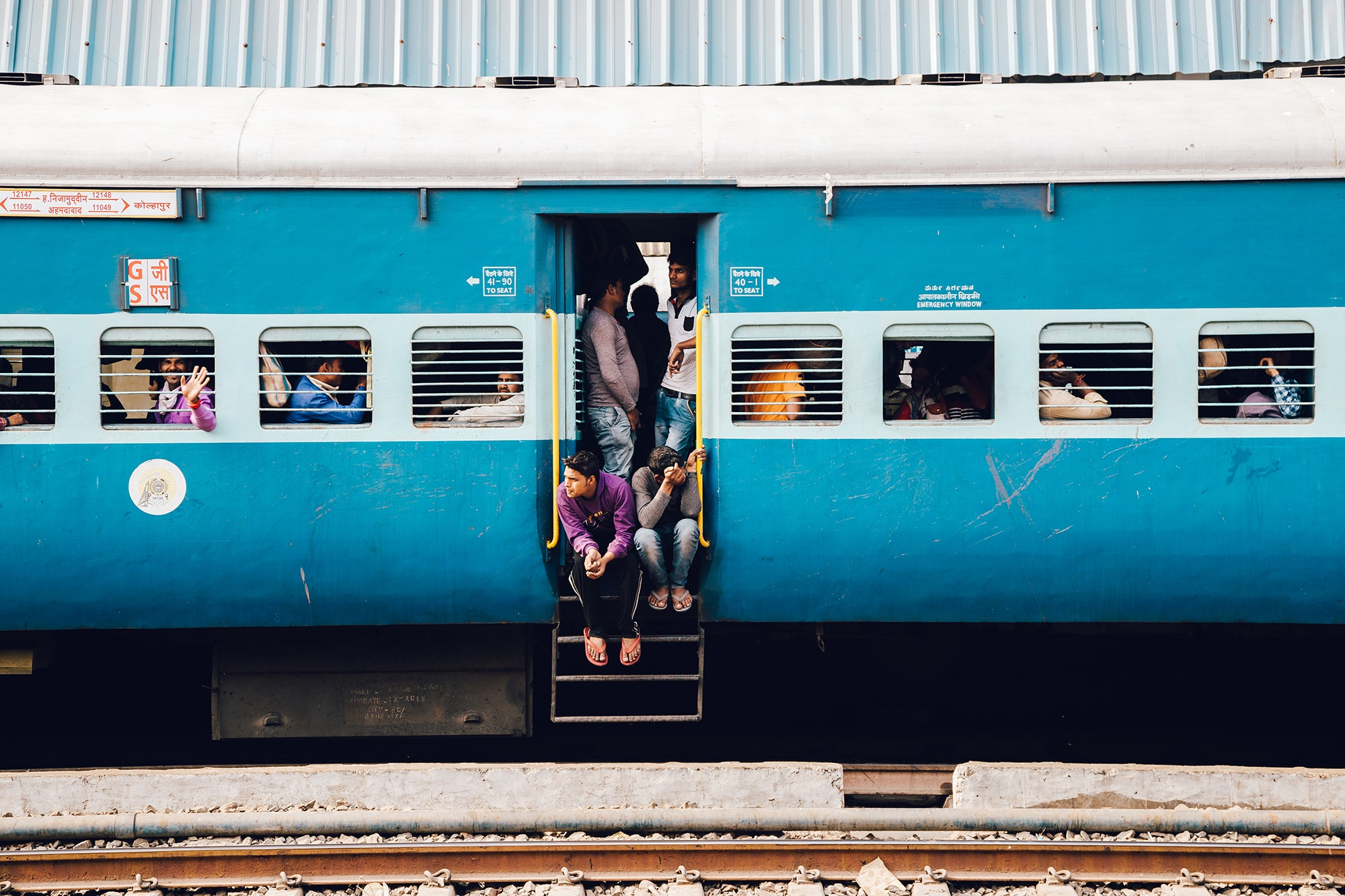 Passengers in the doorway of an Indian train