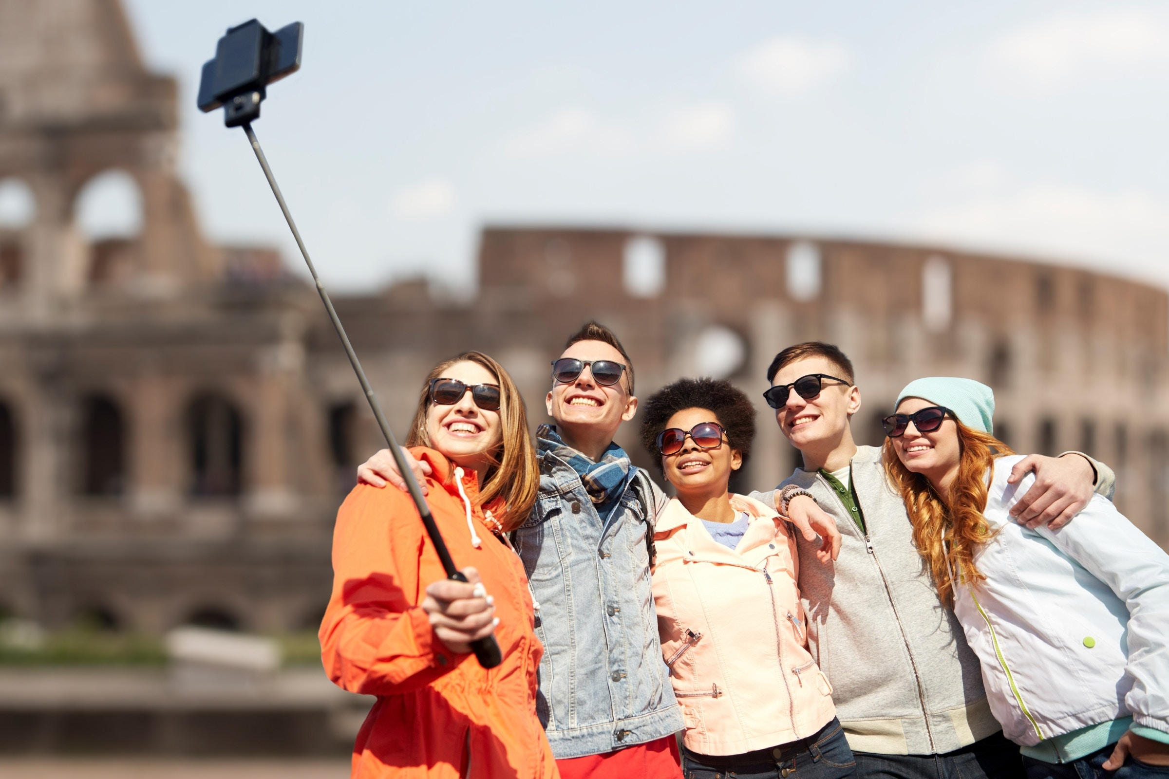 Group of smiling teenage friends taking selfie with smartphone and monopod with the Colosseum ruins in background © Syda Productions / Shutterstock