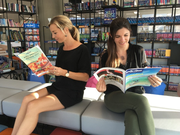 Two staff members read the Lonely Planet magazine and supplement in the Lonely Planet office library