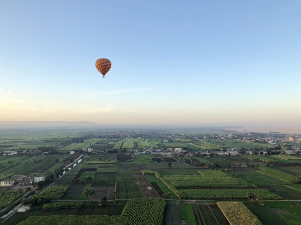 A hot air balloon over the lush green landscapes along the banks of the Nile