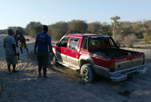 A group of Malagasy men help rescue a 4WD that's got stuck on a sandy road