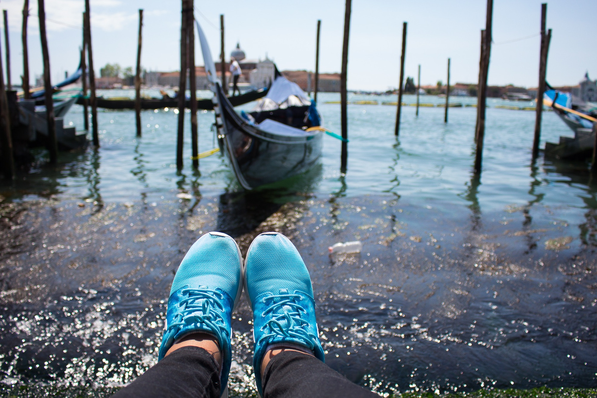 Charlotte's blue trainers dangling over Venice's Grand Canal