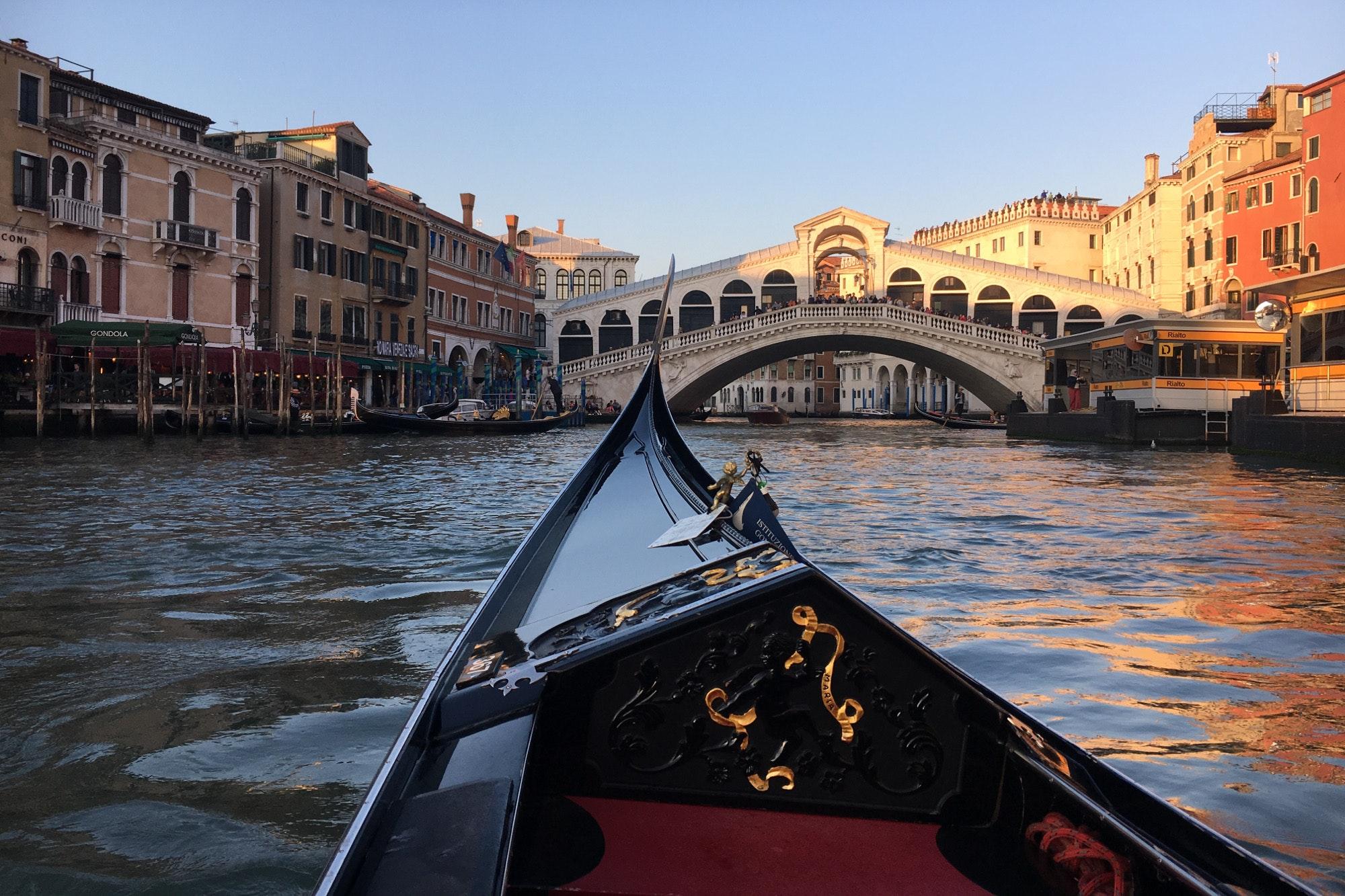 The front of a gondola facing the Rialto Bridge
