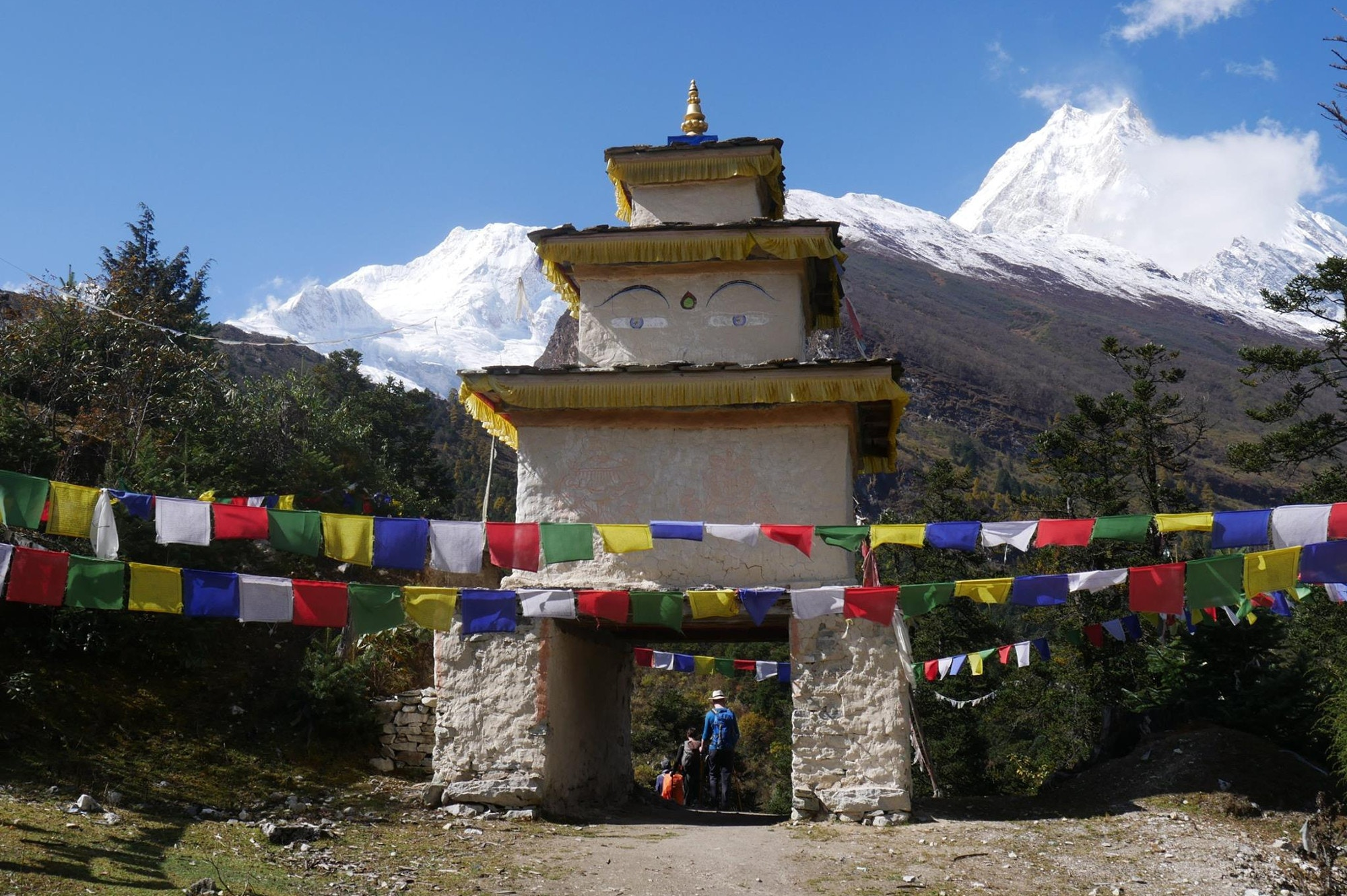 A stupa with Buddha eyes painted on and prayer flags in the foreground