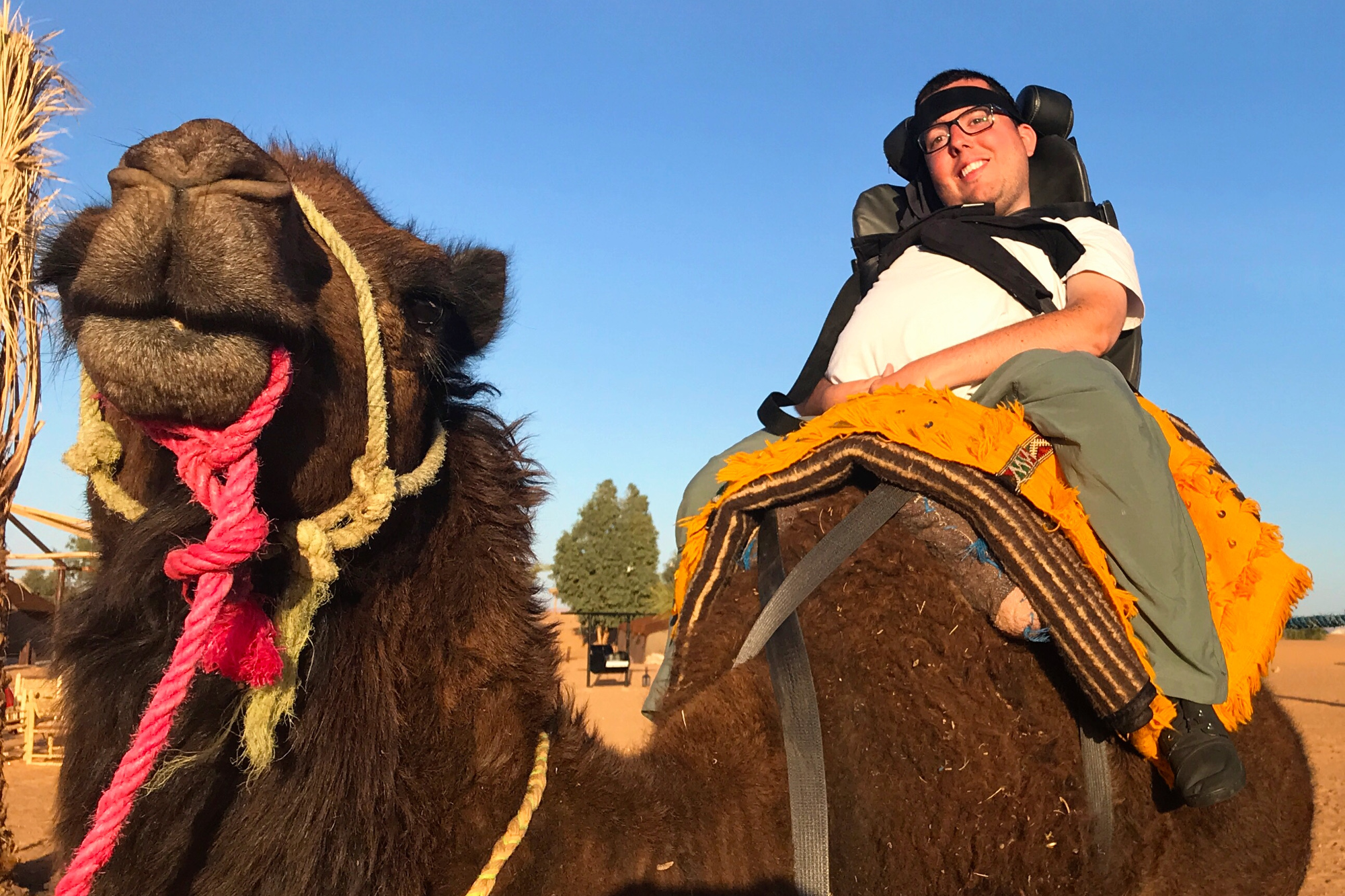 Cory Lee riding a camel in a specially adapted saddle