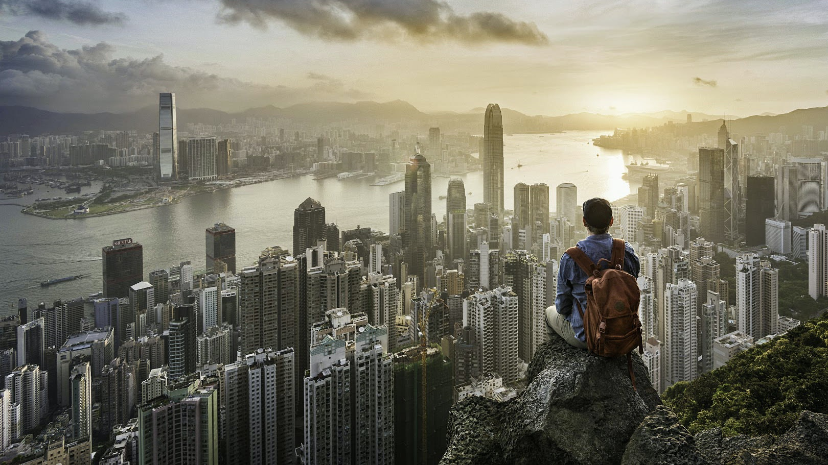 Man sitting on rock in front of Hong Kong skyline at sunrise © Martin Puddy / Getty Images