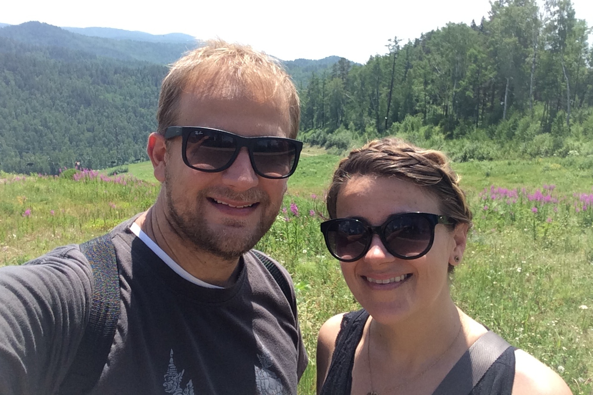 Trisha and her brother taking a selfie in front of a rural vista