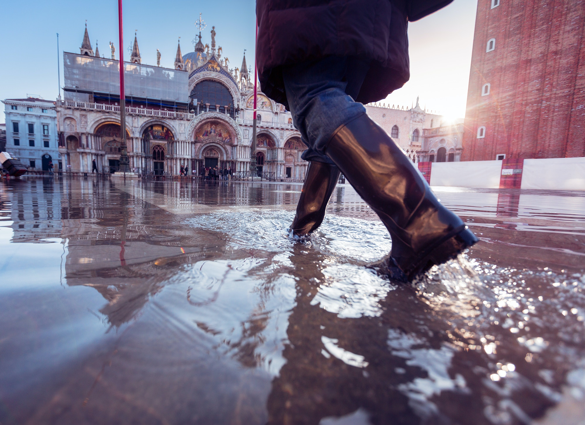 A person in rubber boots walking in Venice's Piazza San Marco © Nullplus / Getty Images