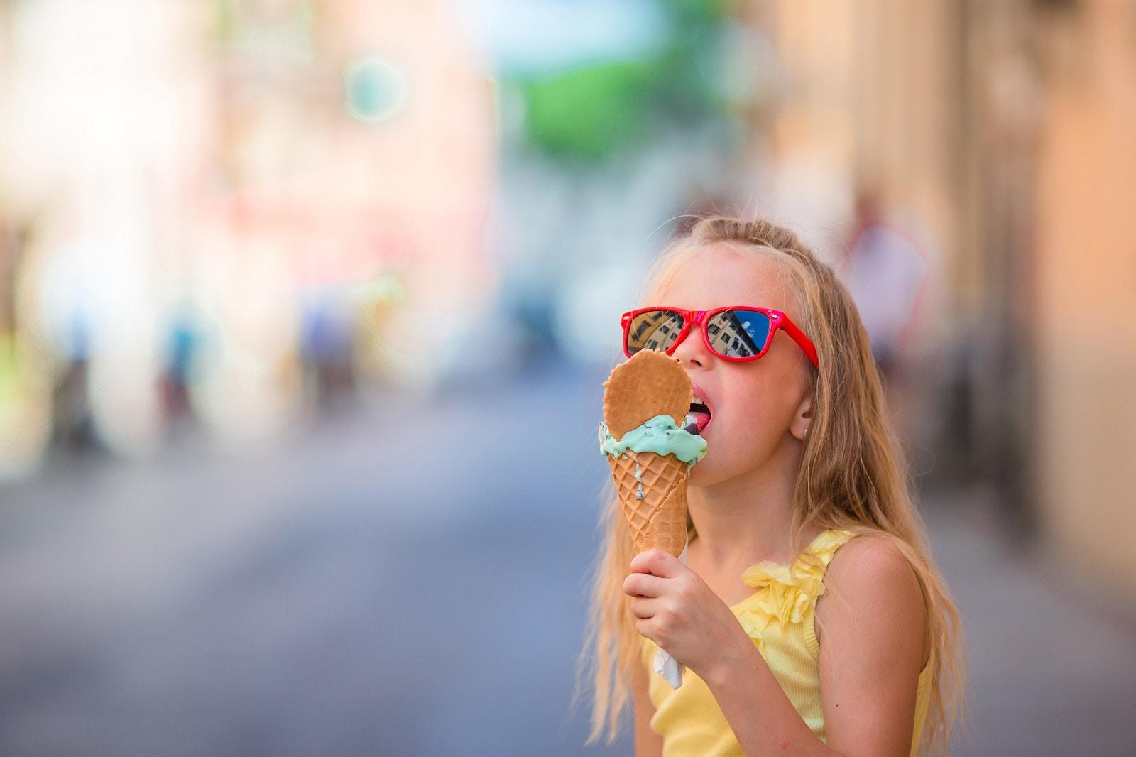 A girl wearing sunglasses eats gelato from a cone in Rome © TravnikovStudio / Shutterstock