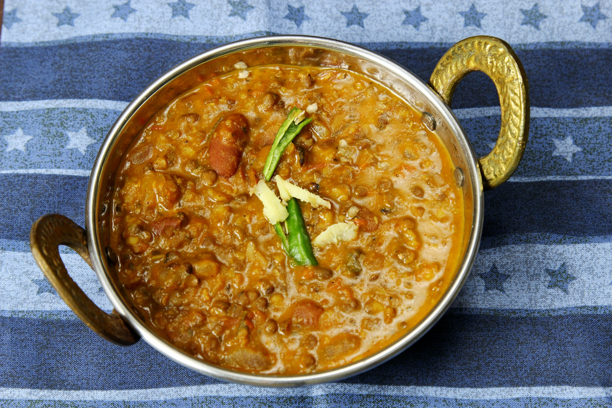 Daal Makhani in a kadhai serving dish on a blue background © DipaliS / Getty Images
