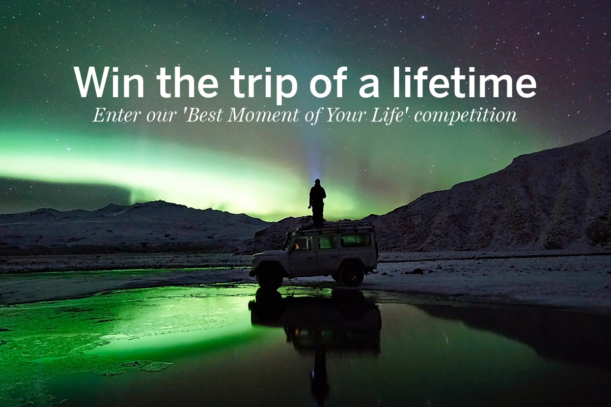 Win the trip of a lifetime - a figure observes the northern lights from the roof of a jeep