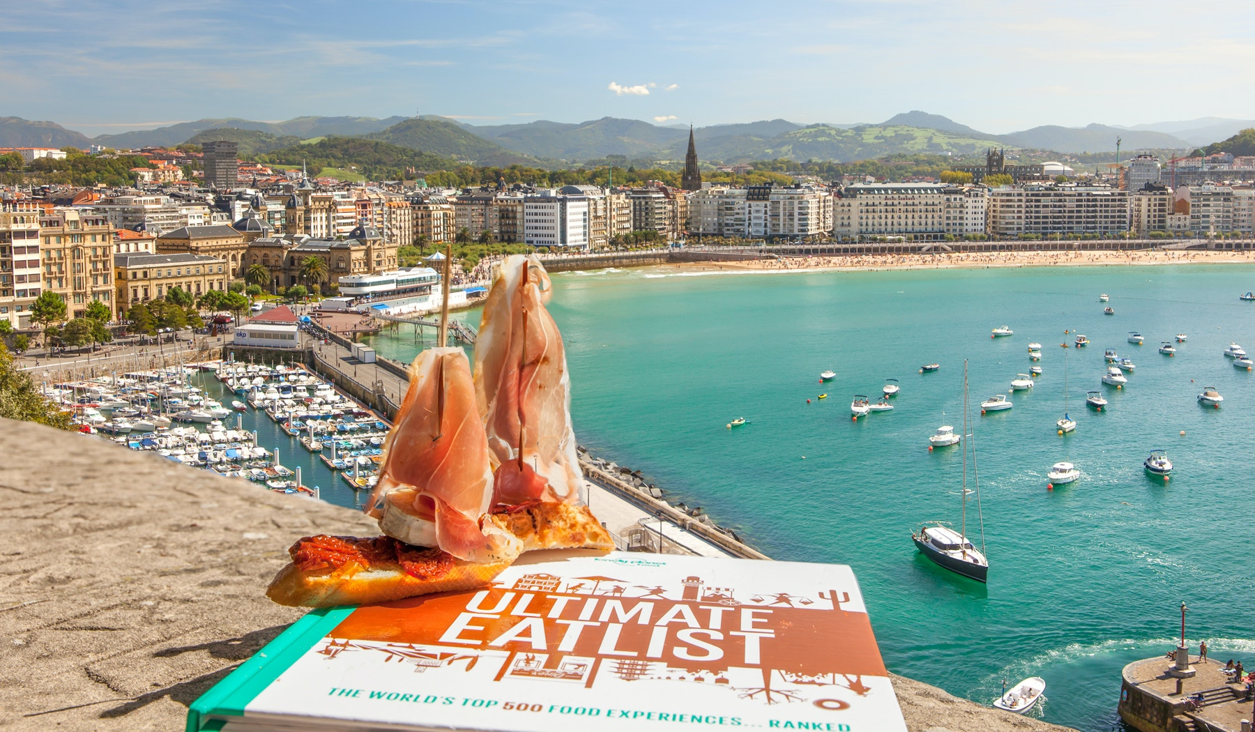 Two pintxos are shown resting on top of a copy of Lonely Planet's Ultimate Eats book, with the harbour of San Sebastián in the background
