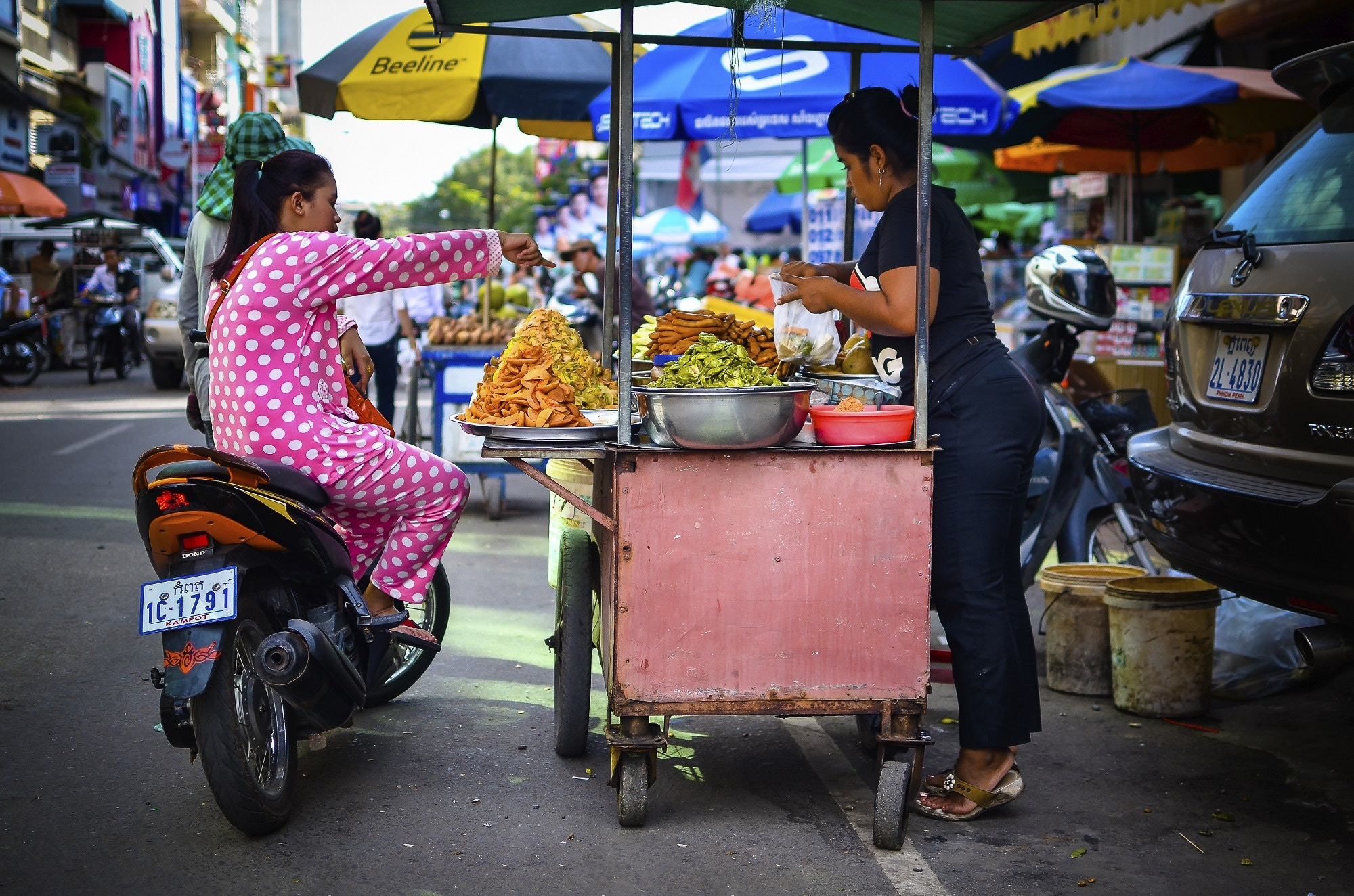 A woman on a motorbike orders snacks from a street food stall in Phnom Penh, Cambodia