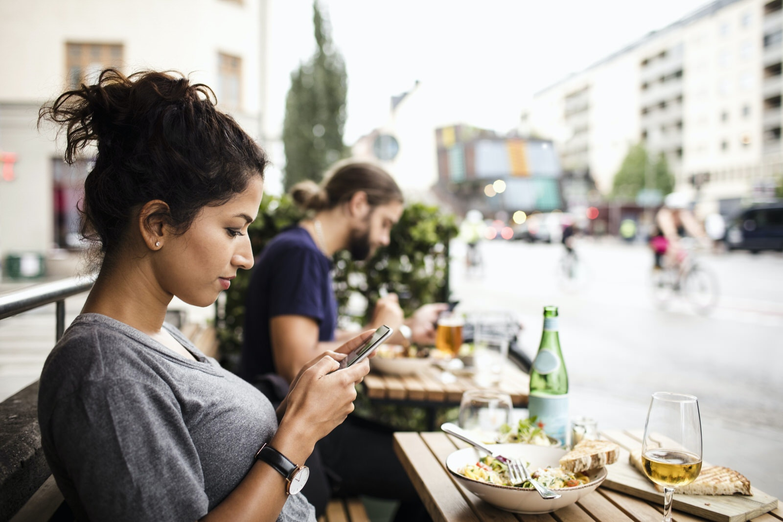 Side view of woman text messaging while having food at sidewalk cafe in city, Sodermalm, Stcokholm.