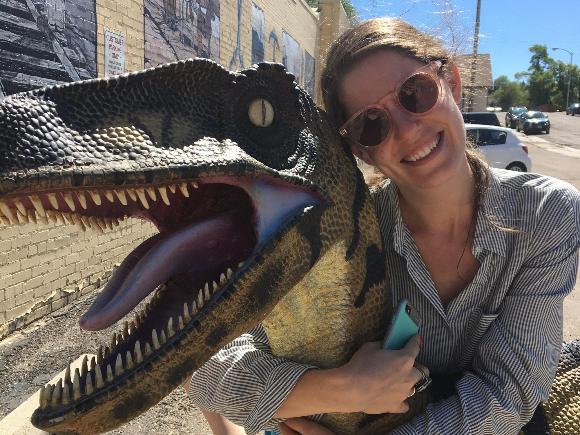 Hannah hugging a model of a dinosaur © Hannah Karns