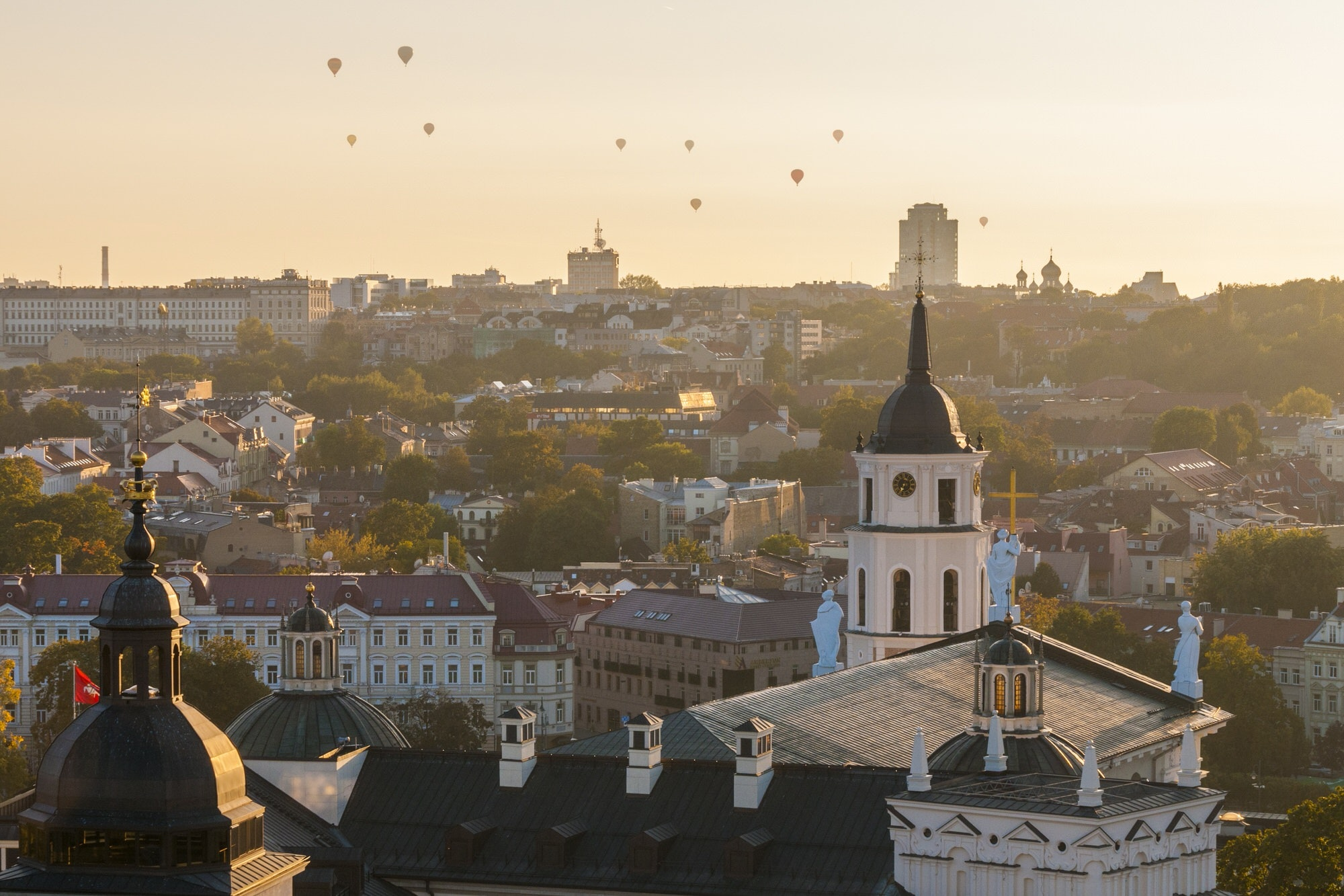 Hot-air balloons flying over city of Vilnius at sunset