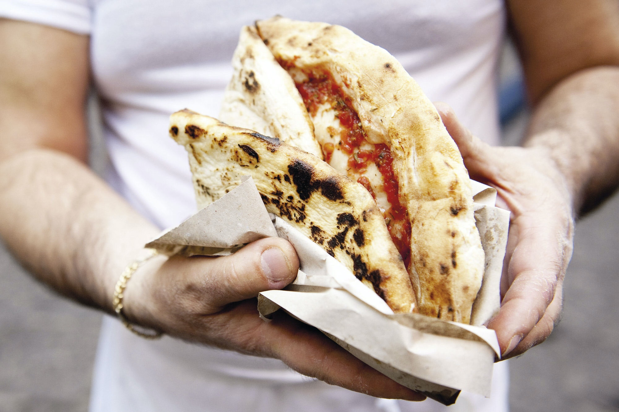 A man holding a typical Neapolitan Margherita pizza