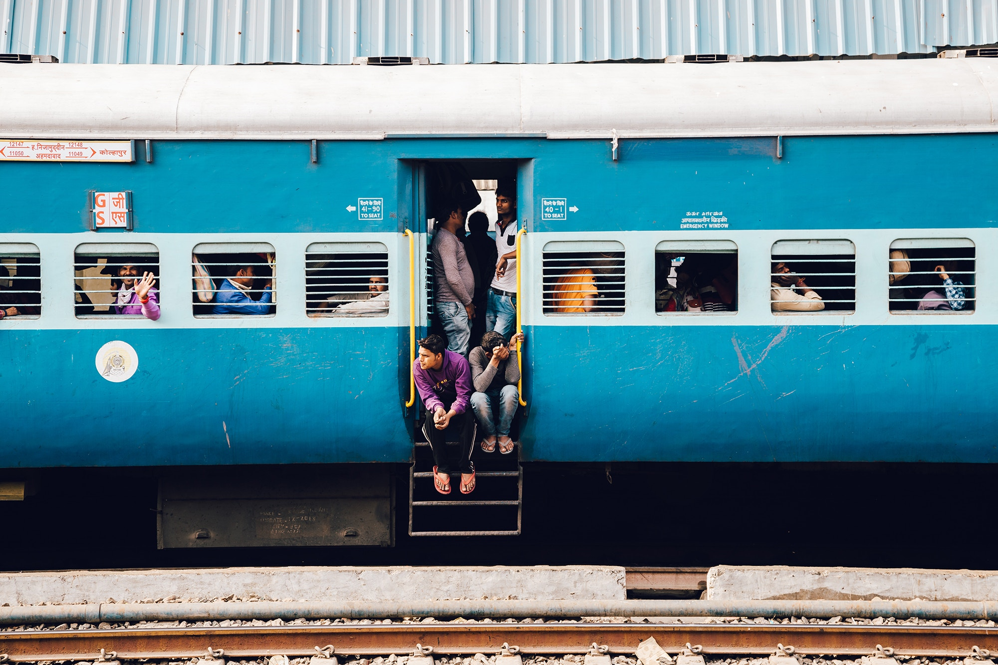 Passengers in the doorway of an Indian train