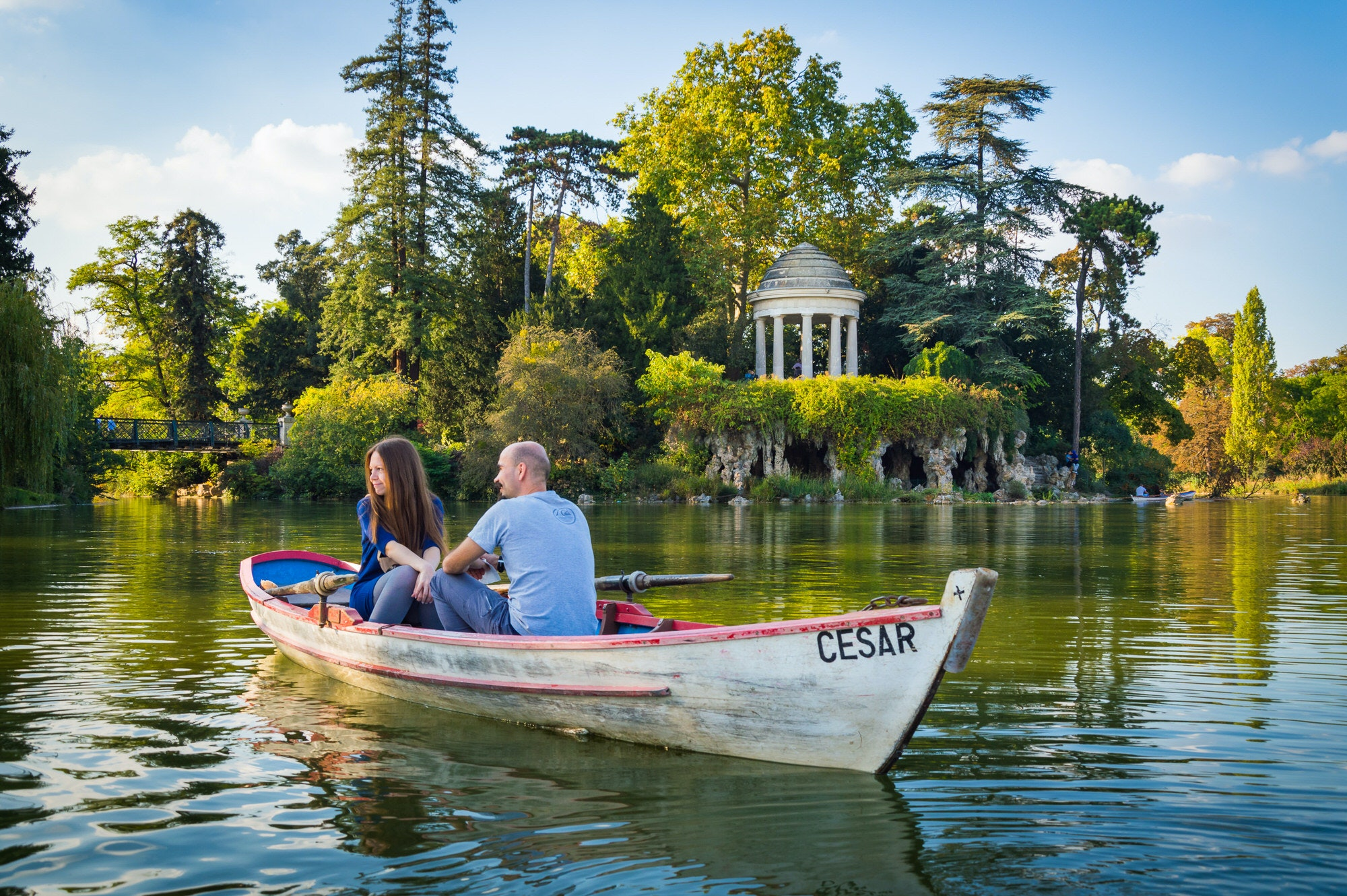 A couple in a row boat at Bois de Vincennes with the Temple of Love in the background