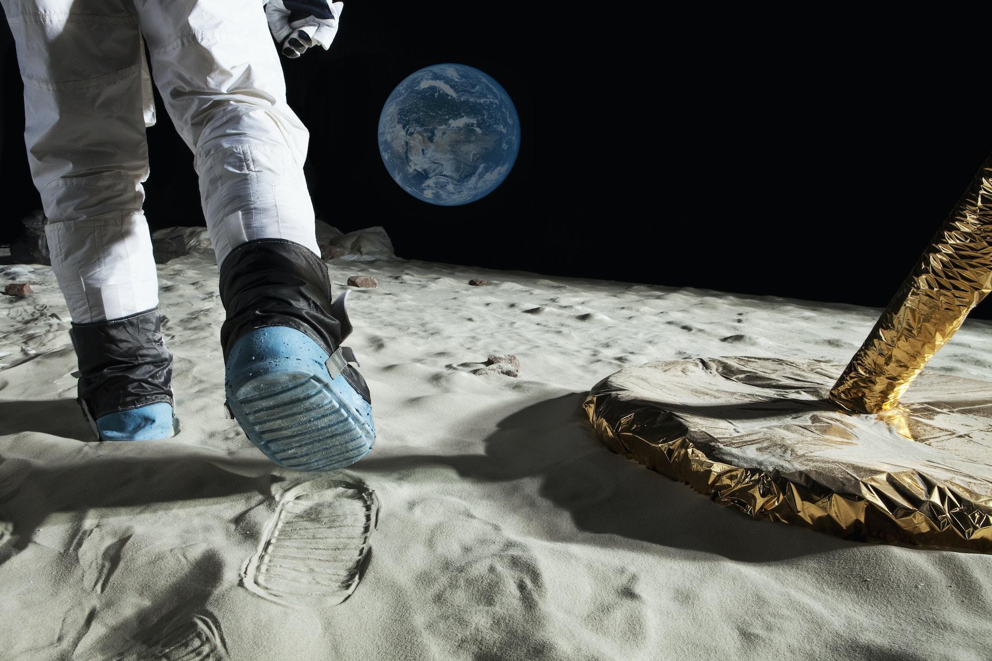 Un astronauta caminando en la Luna con la Tierra elevándose en el fondo