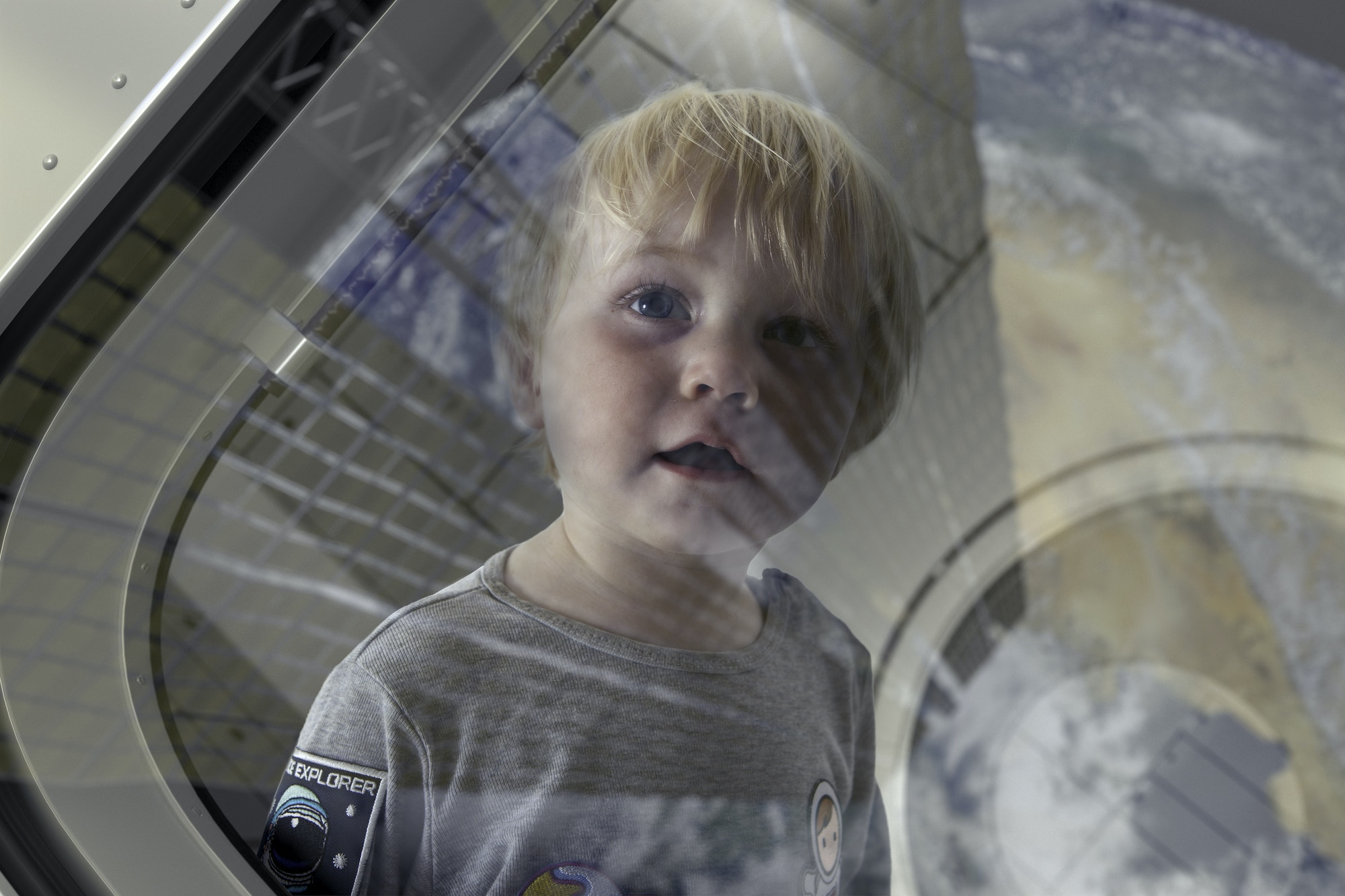 A young boy looks at the surface of a planet from the window of a spaceship