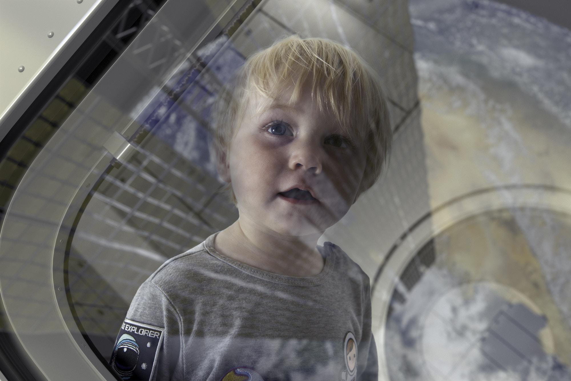 Un niño mira la superficie de un planeta desde la ventana de una nave espacial