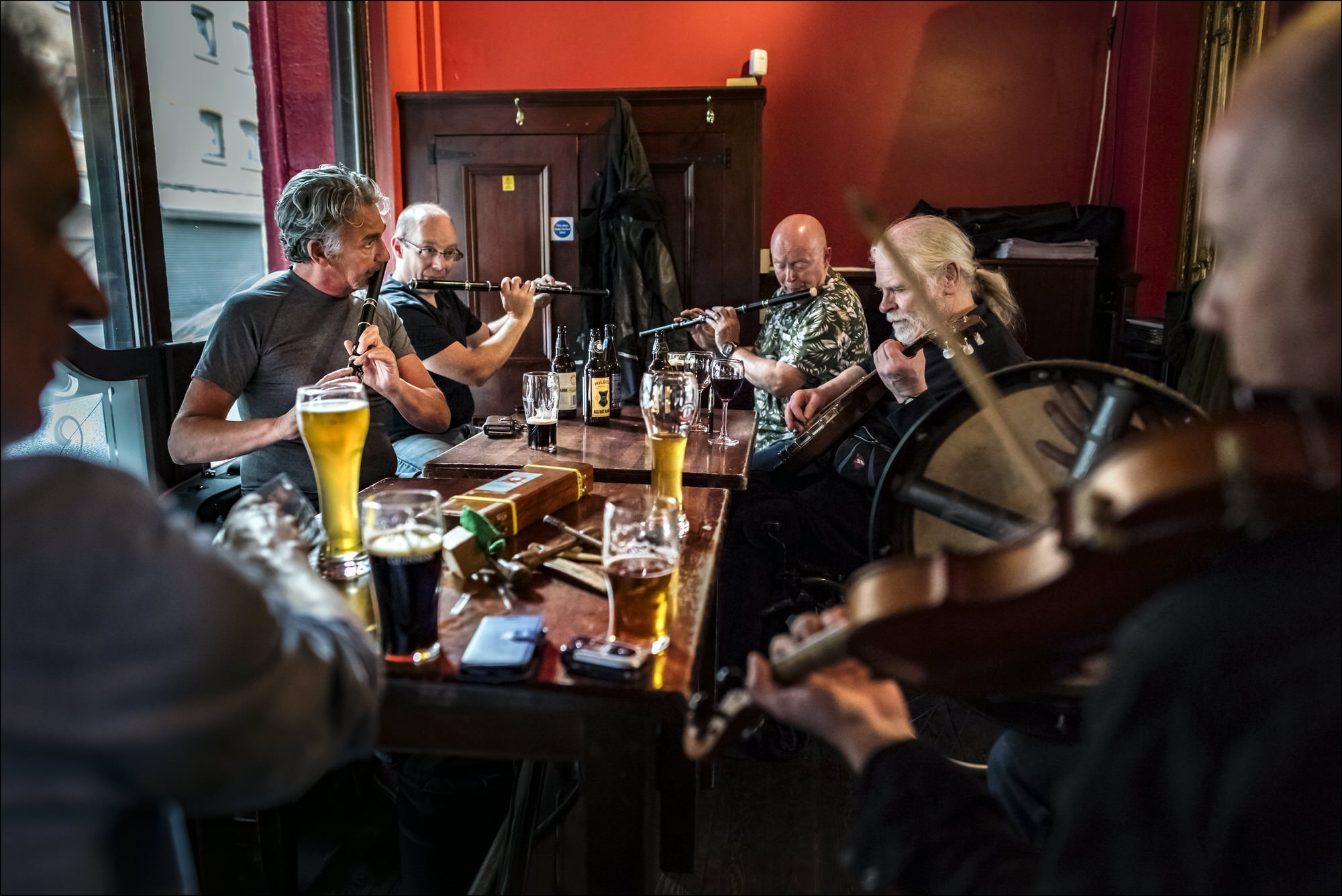 Irish musicians perform while seated on a table at the John Hewitt pub in Belfast