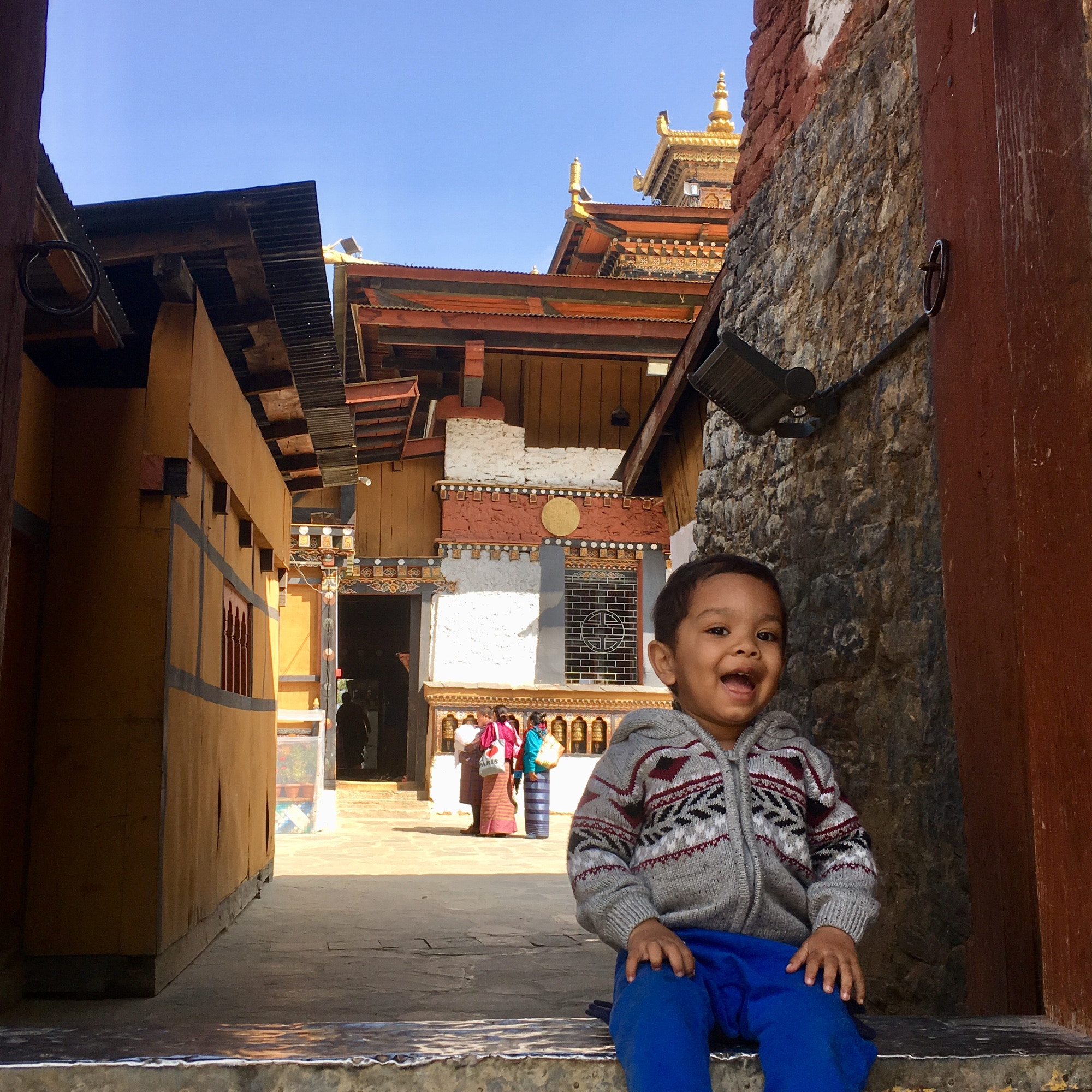 Samai's son on the steps of a 12th-century monastery in Bhutan