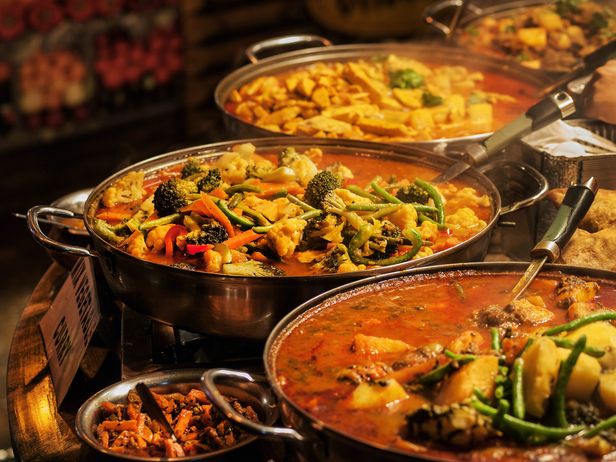 A selection of vegetable curries at an Indian takeaway in a London market