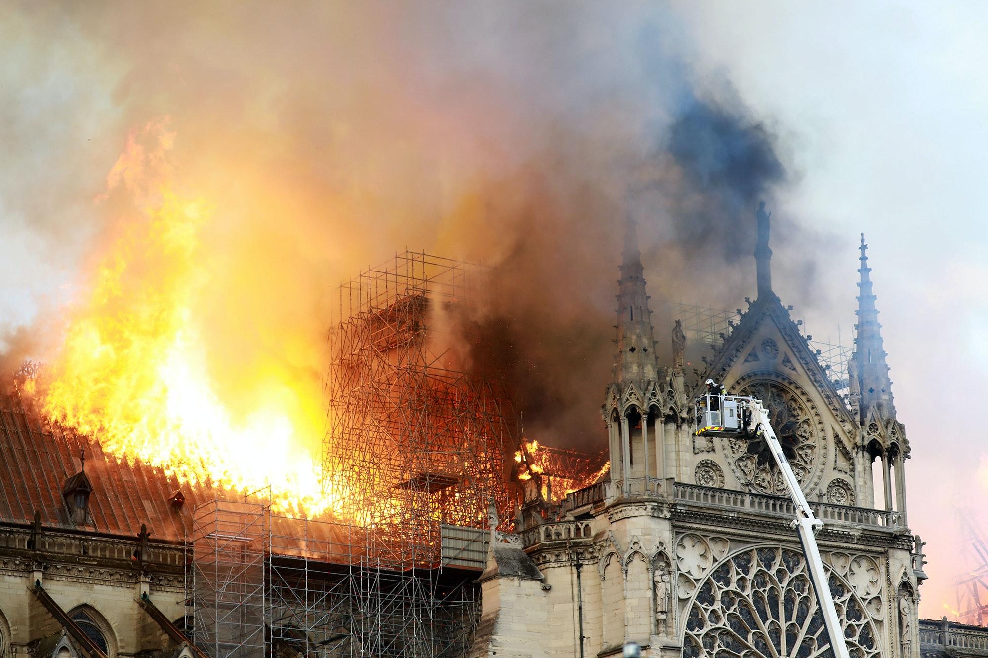 Firefights battling the blaze yesterday as it spread across the roof of Cathédrale Notre Dame de Paris