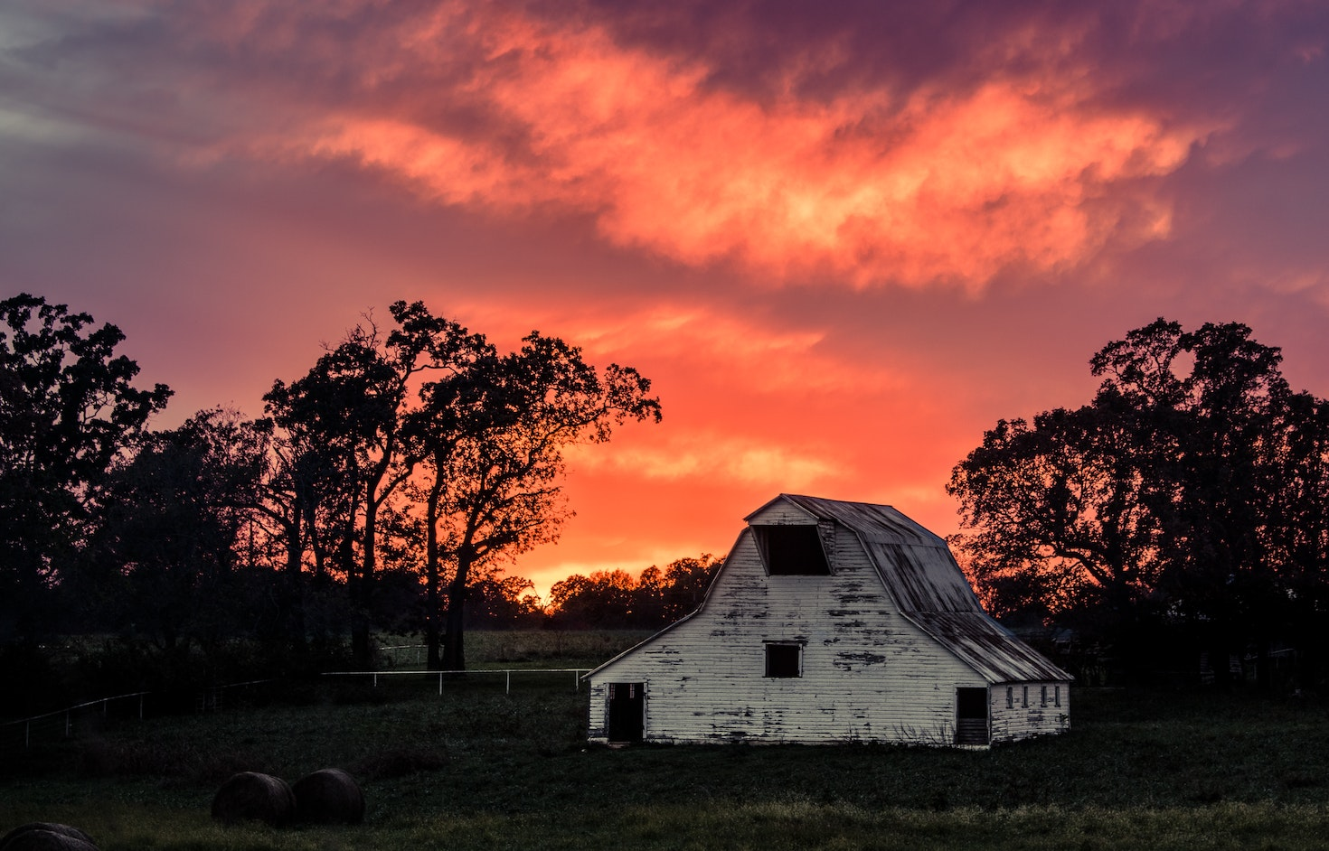 Sunset fades behind a long standing barn along AR 112 on the outskirts of Bentonville, Arkansas © Chris Works / 500px